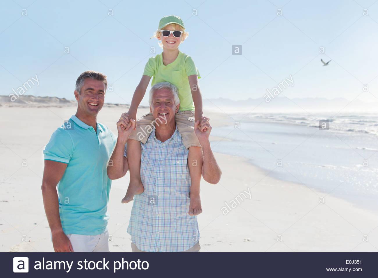 Multi-generation men on sunny beach - Stock Image