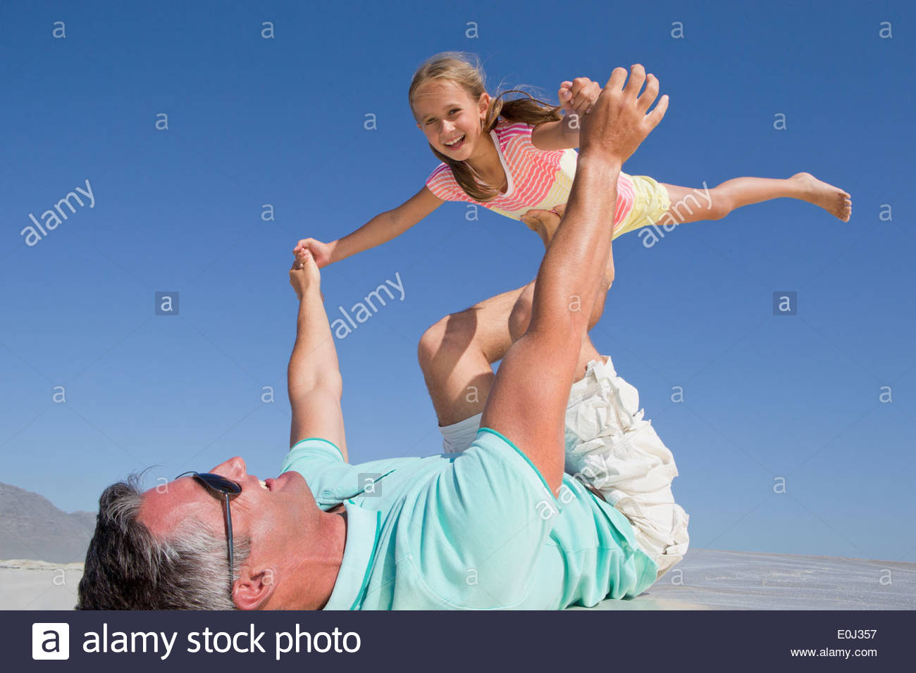Father lifting daughter on sunny beach - Stock Image