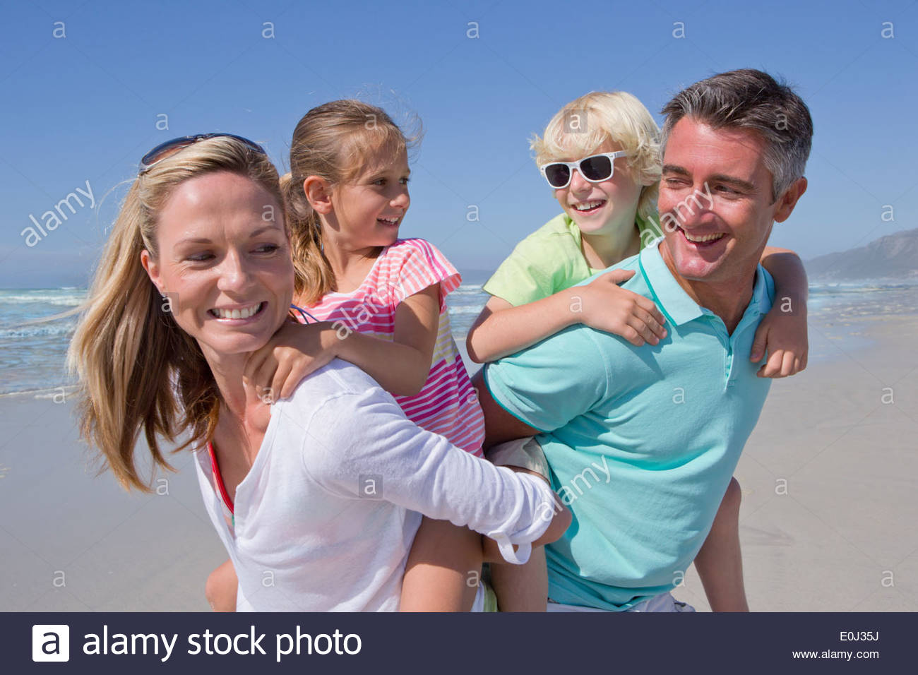Parents piggybacking children on sunny beach - Stock Image