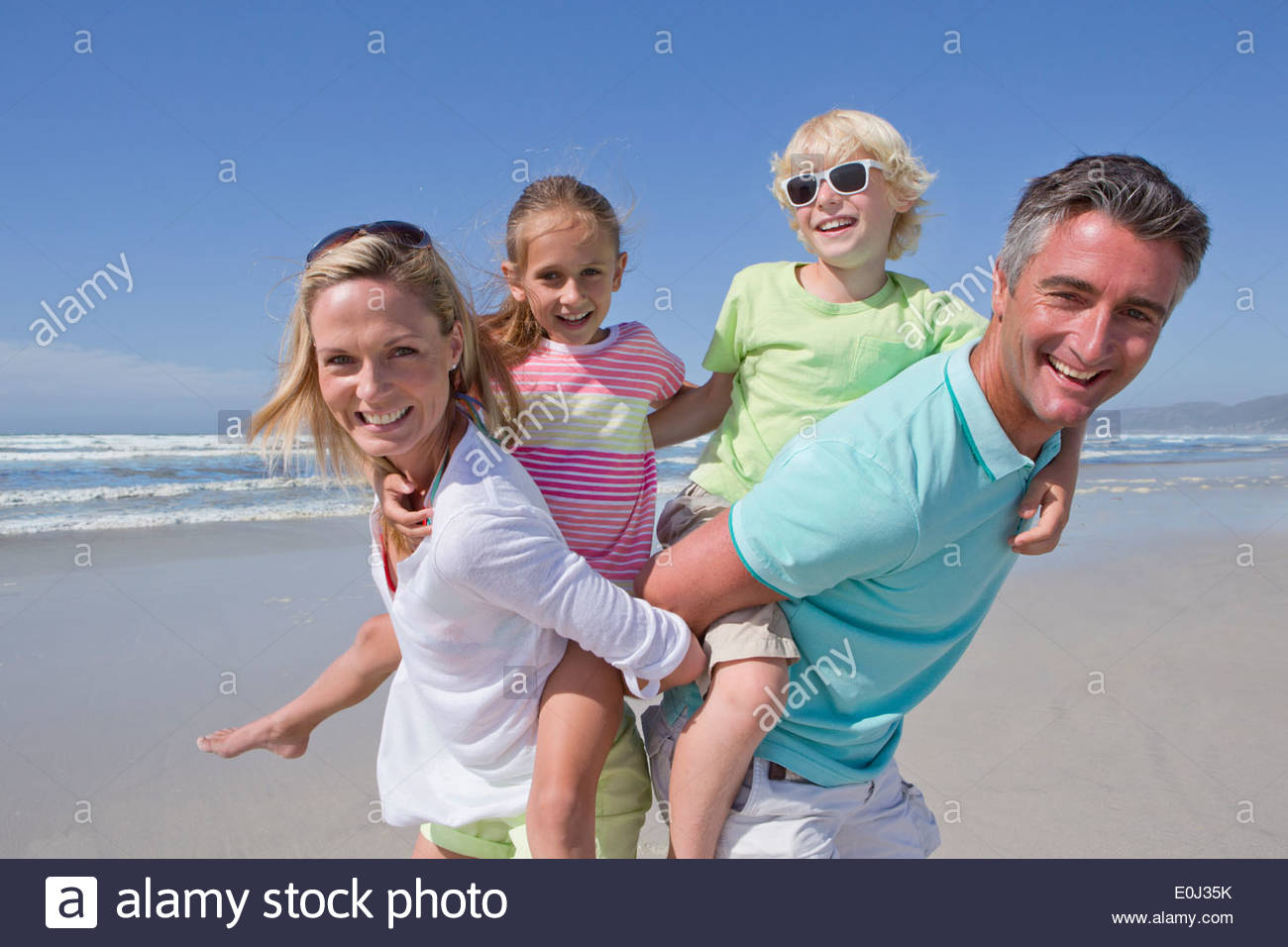Portrait of smiling parents piggybacking children on sunny beach - Stock Image