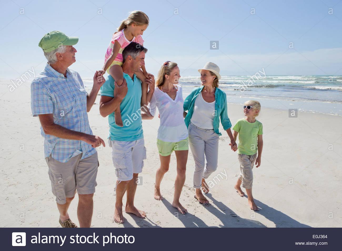 Multi-generation family walking on sunny beach - Stock Image