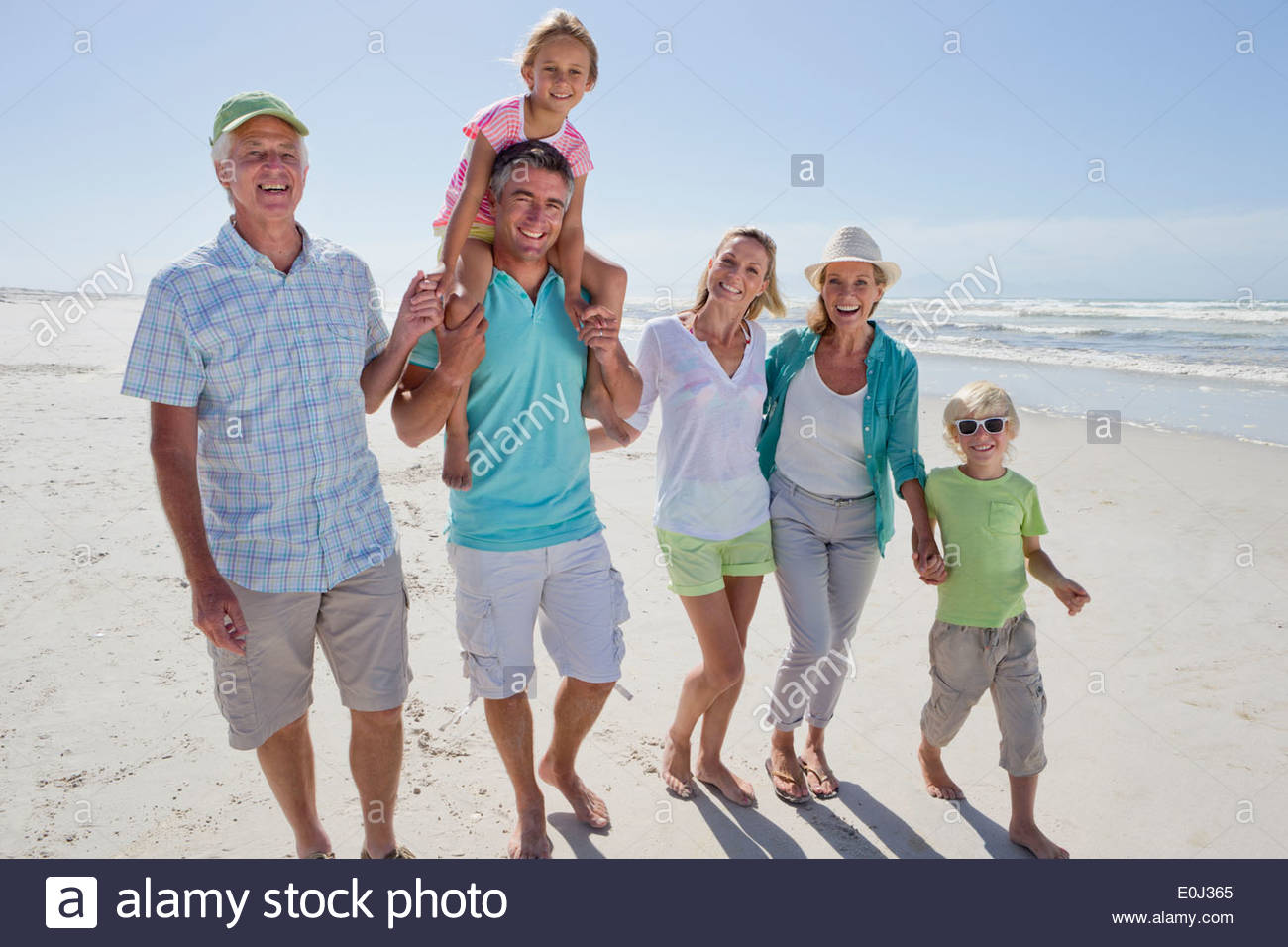 Portrait of smiling multi-generation family walking on sunny beach - Stock Image