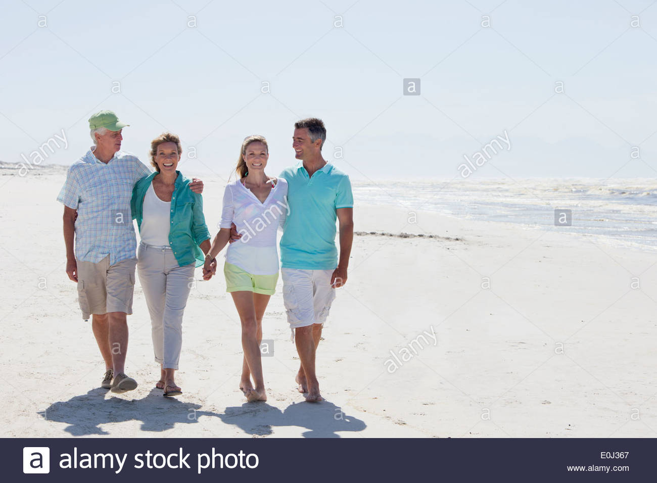 Happy couples walking on sunny beach - Stock Image
