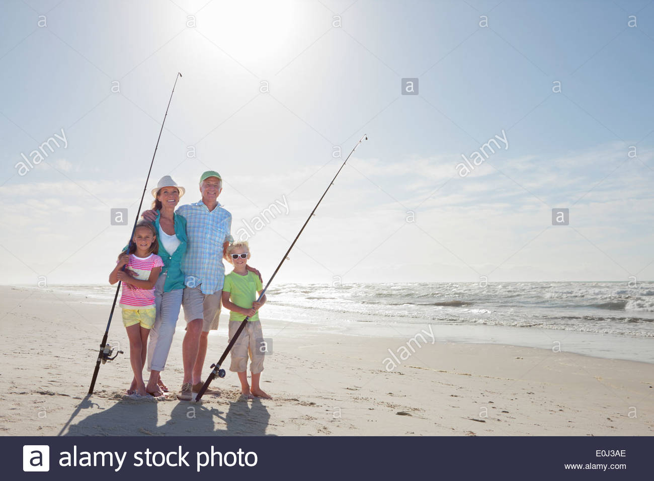 Portrait of grandparents and grandchildren with fishing rods on sunny beach - Stock Image