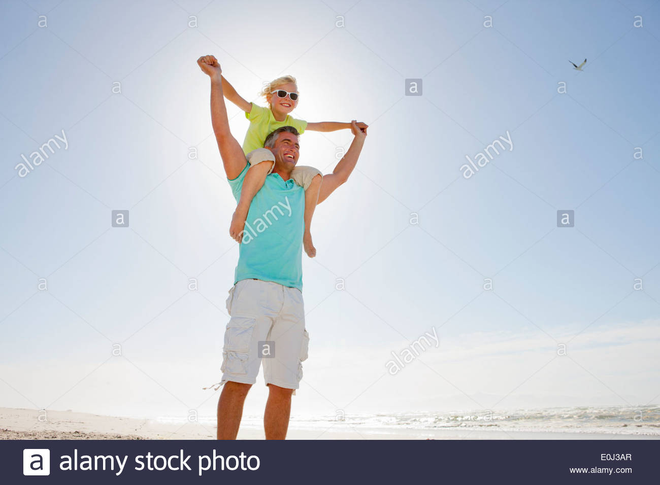 Father carrying son on shoulders on sunny beach - Stock Image