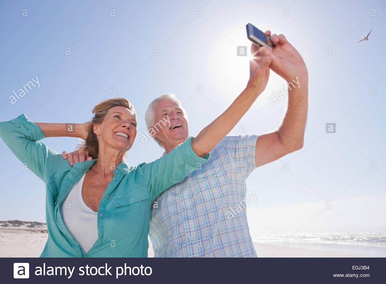 Senior couple with digital camera taking self-portrait on sunny beach - Stock Image