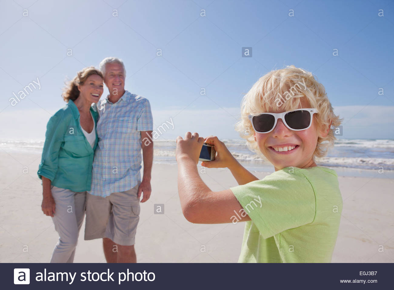 Portrait of smiling grandson with digital camera photographing grandparents on sunny beach - Stock Image