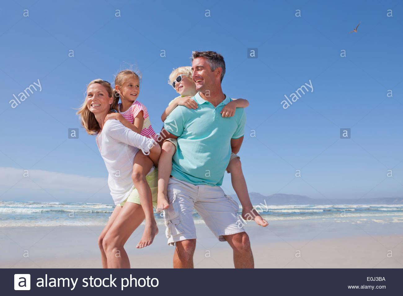 Parents piggybacking children on sunny beach - Stock Image