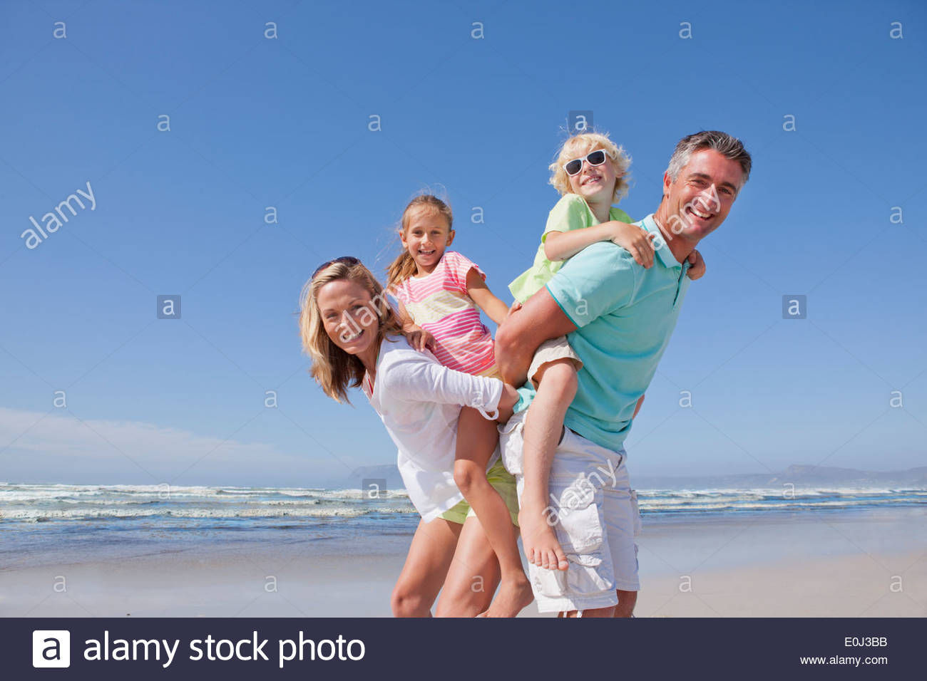 Portrait of smiling parents piggybacking children on sunny beach - Stock Image