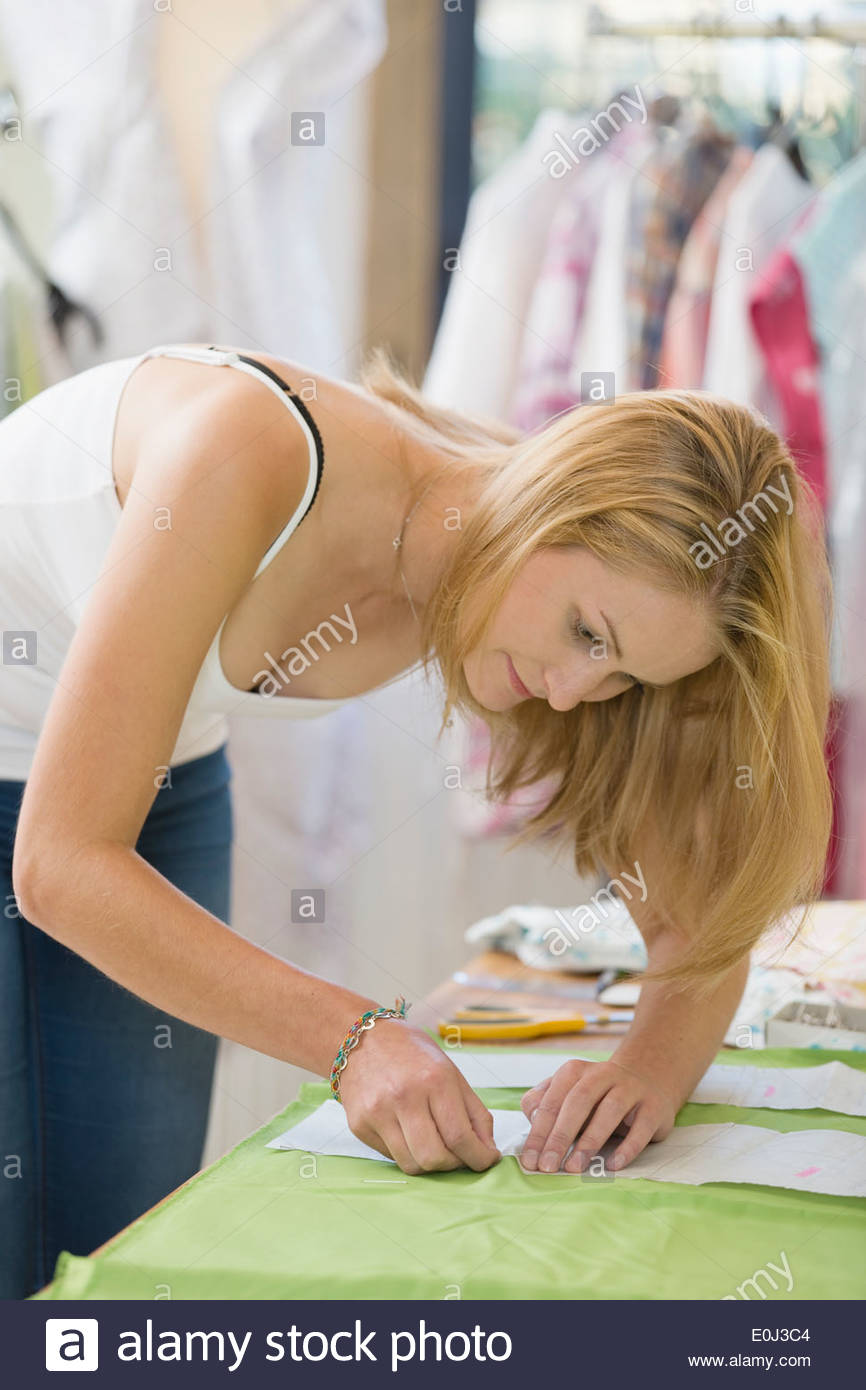 Fashion Designer Sewing Fabric In Studio - Stock Image