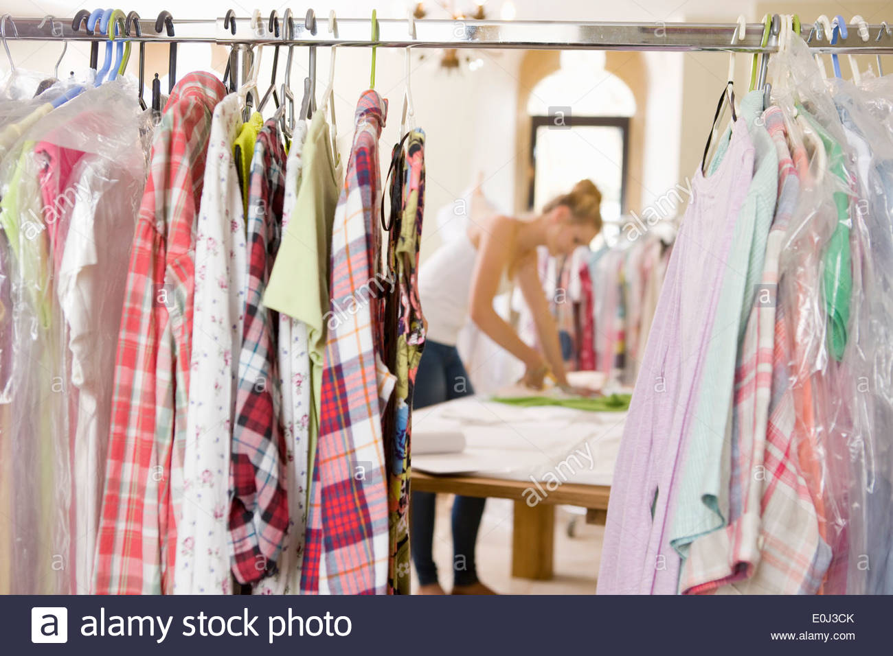 Fashion Designer Cutting Out Pattern From Fabric In Studio - Stock Image