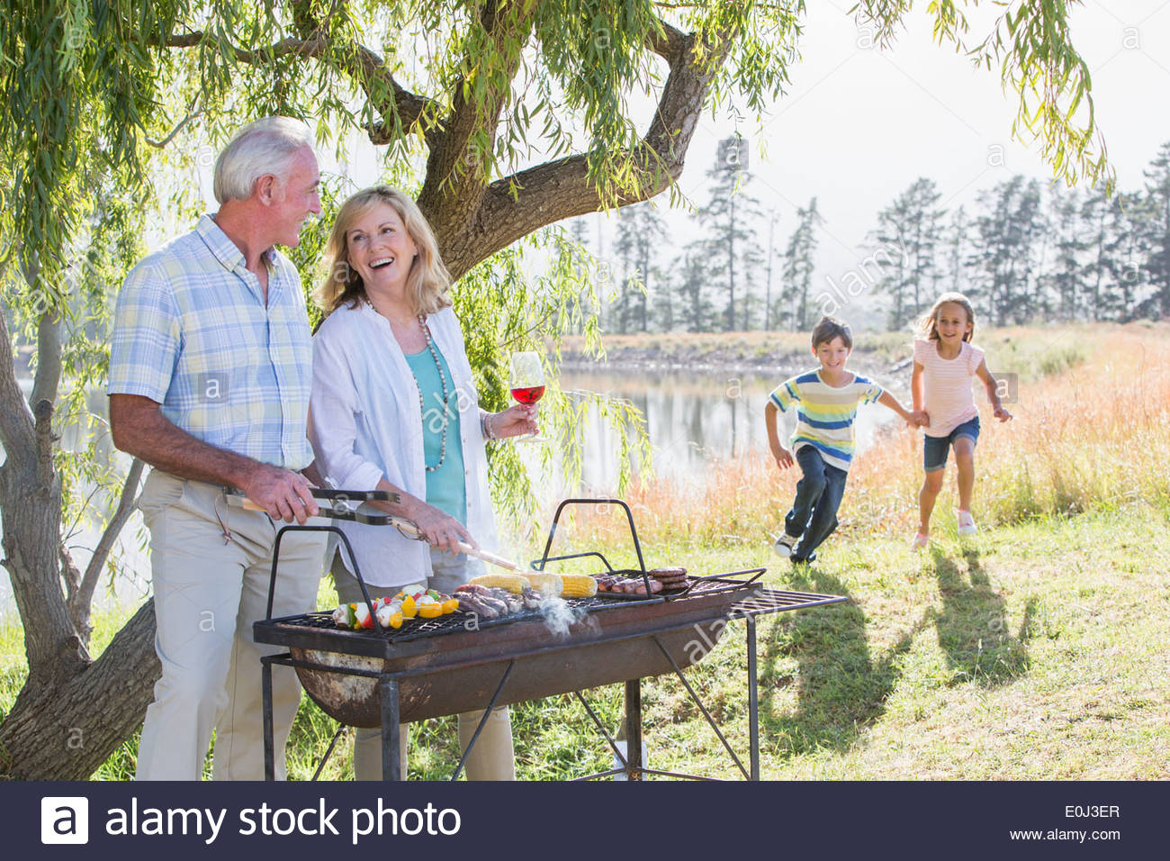 Grandparents Serving Grandchildren At Family Barbeque - Stock Image