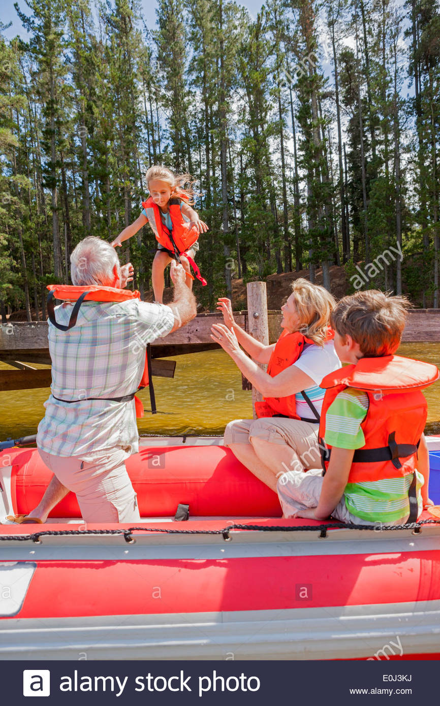 Grandparents And Grandchildren Enjoying Boat Trip On Lake - Stock Image