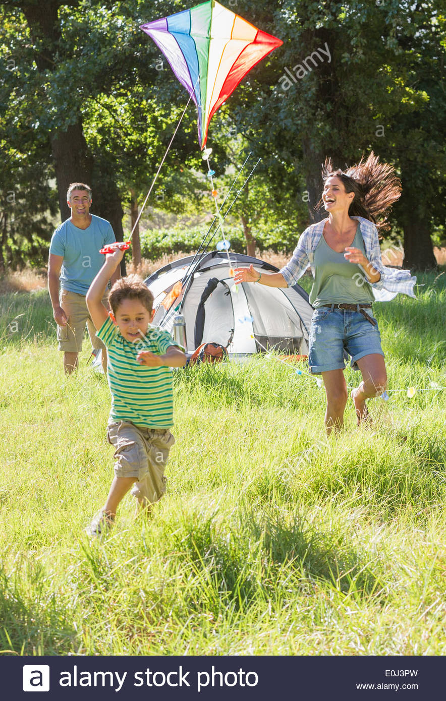 Family Flying Kite On Camping Holiday In Countryside - Stock Image
