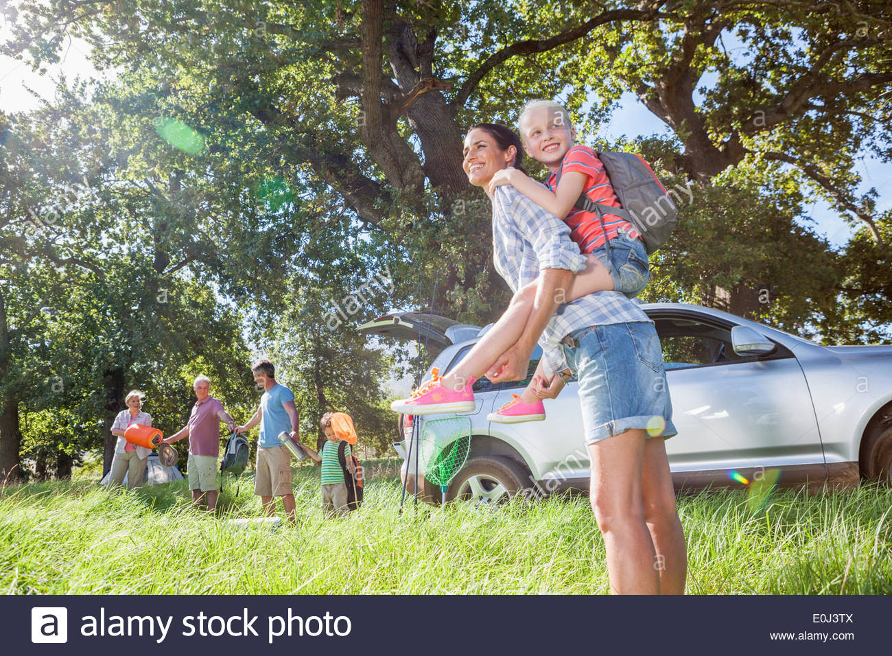 Multi-Generation Family Unpacking Car On Camping Trip - Stock Image