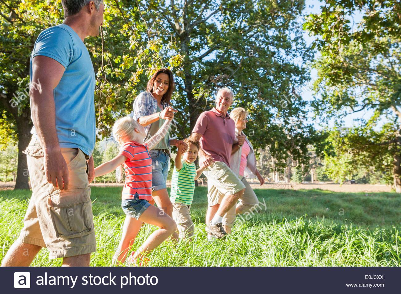 Multi-Generation Family Enjoying Walk In Beautiful Countryside - Stock Image