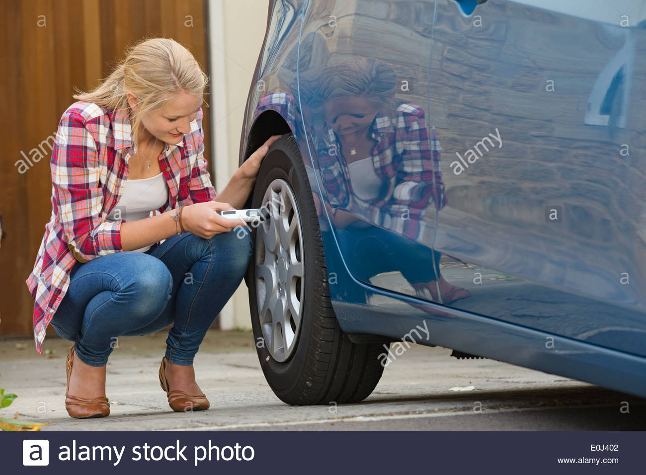 Woman Checking Tyre Pressure On Car - Stock Image