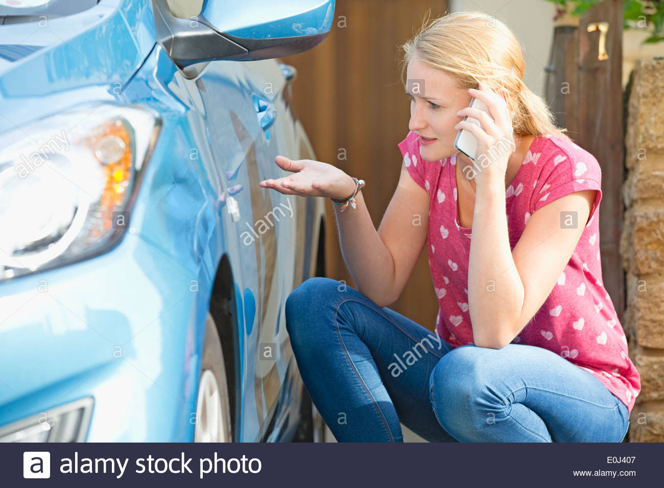 Woman Phoning Insurance Company To Report Car Damage - Stock Image