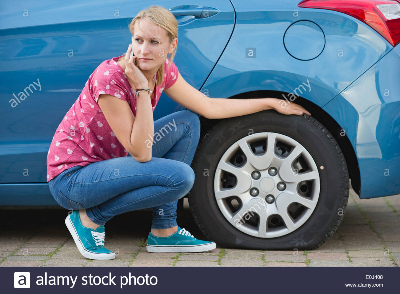 Woman With Flat Tyre On Car Phoning For Assistance - Stock Image