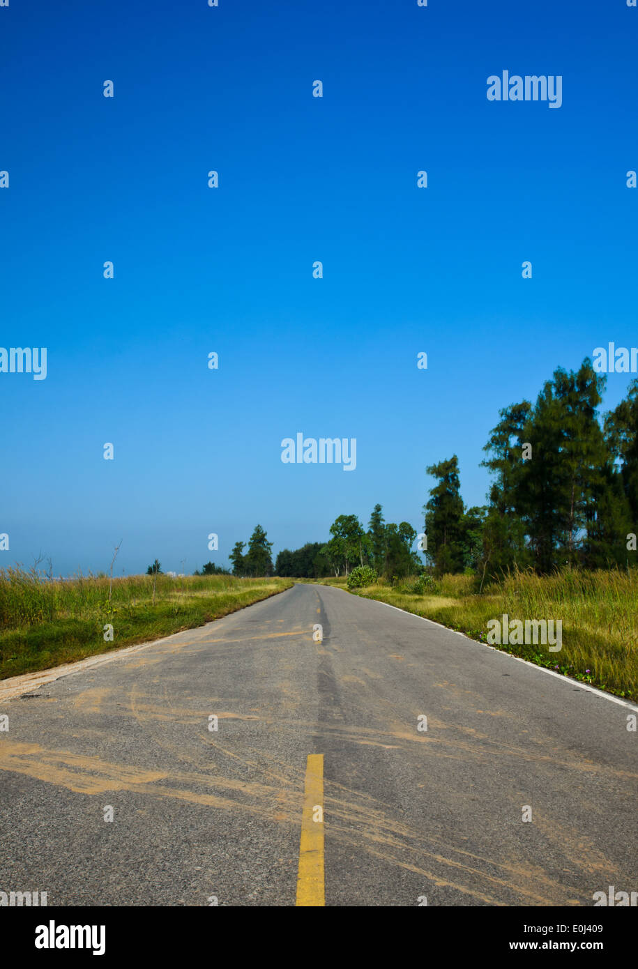 Long road stretching out into the distance under a dramatic blue sky Stock Photo