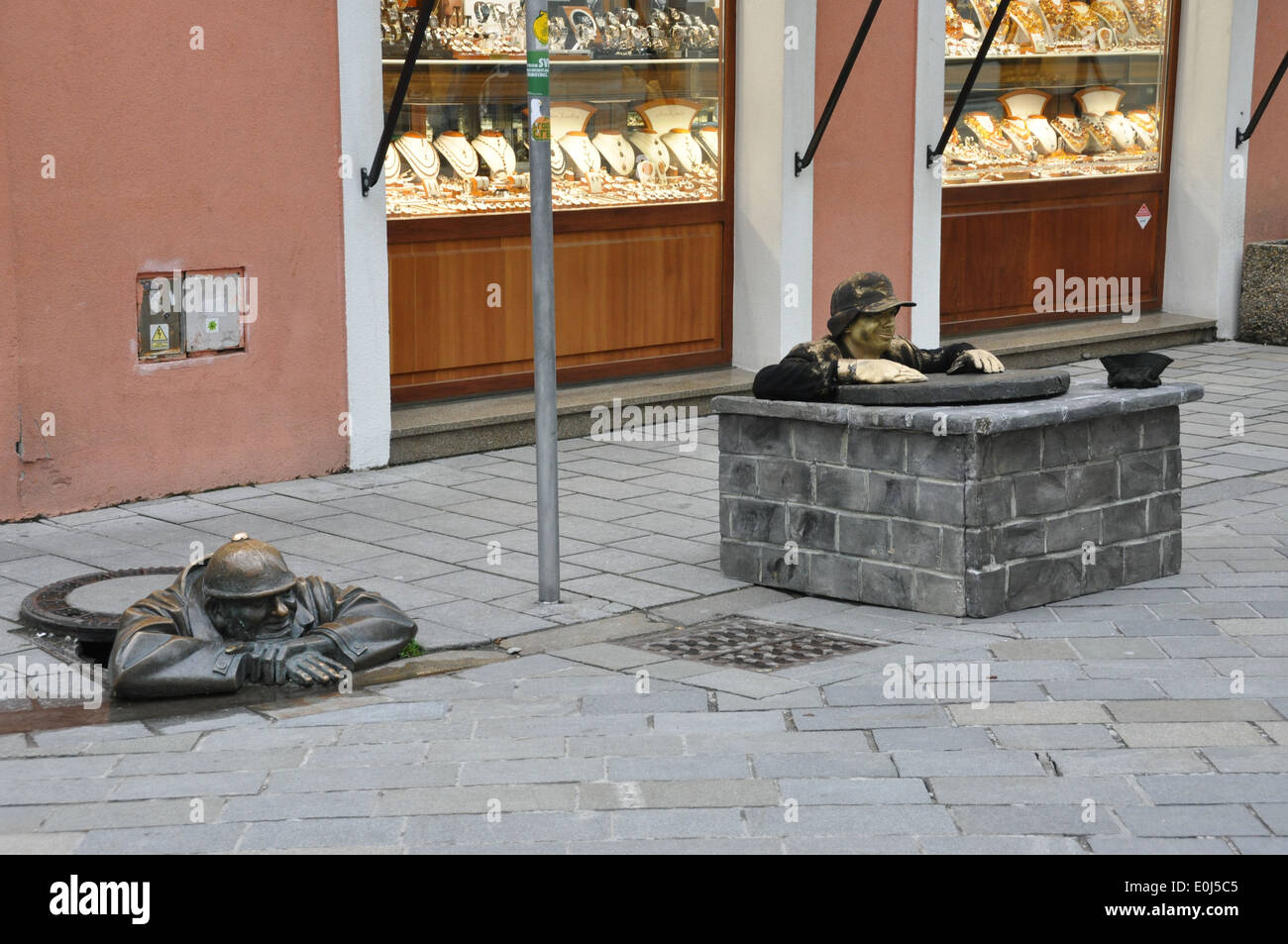 A busker mimicking a statue in Bratislava's Old Town. - Stock Image