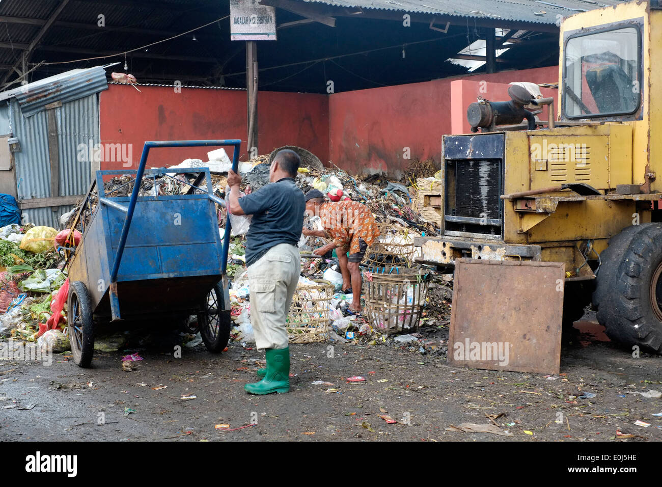 local man working on pile of fetid rubbish at a public dump in malang indonesia - Stock Image