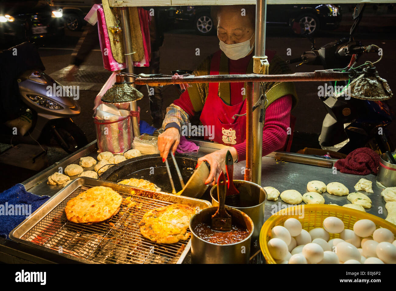 Woman cooking green onion pancakes at food stand in Taiwan - Stock Image