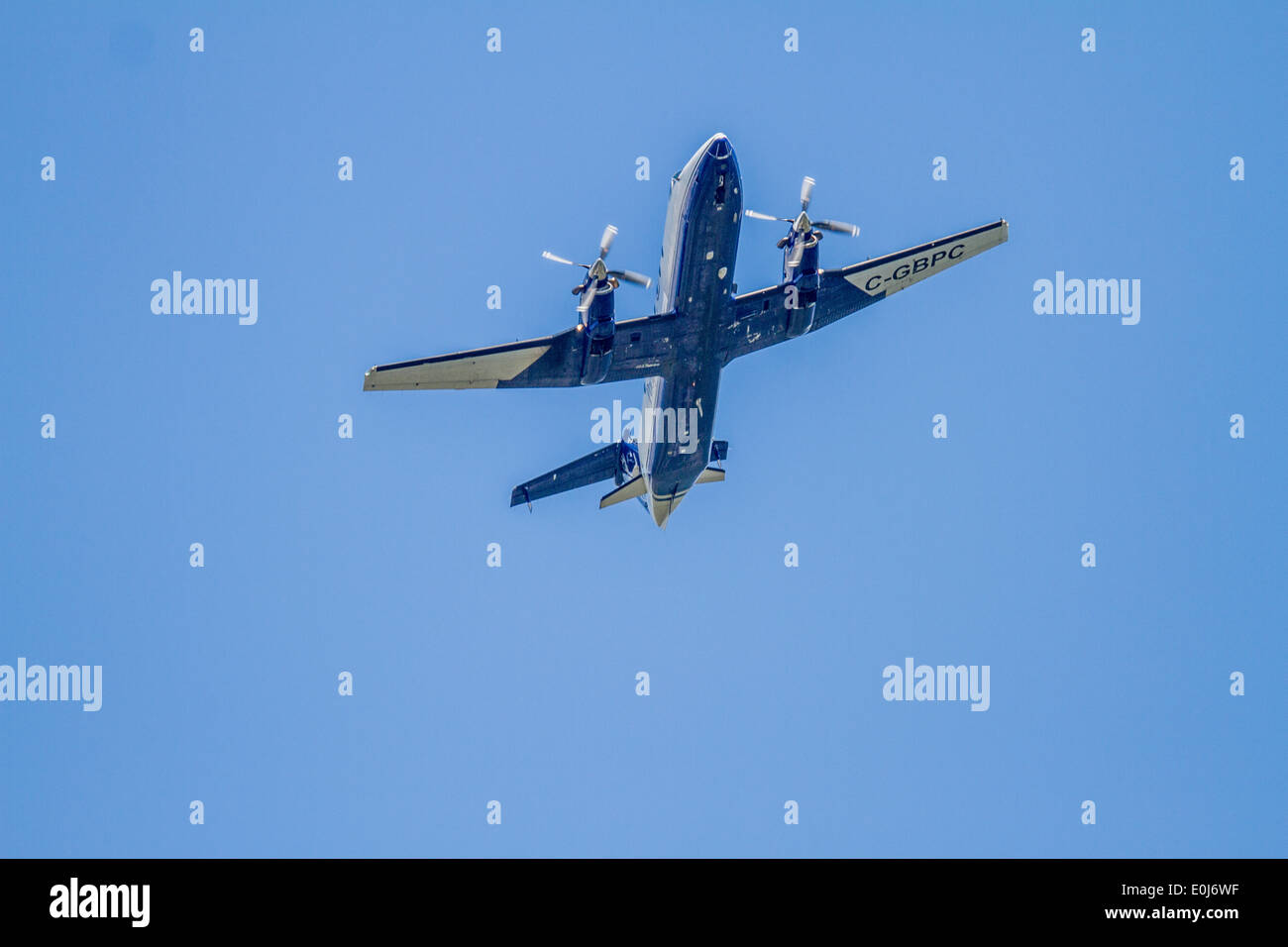 Beech 1900C-2. Twin prop airplane banking and overhead against a blue sky. Stock Photo