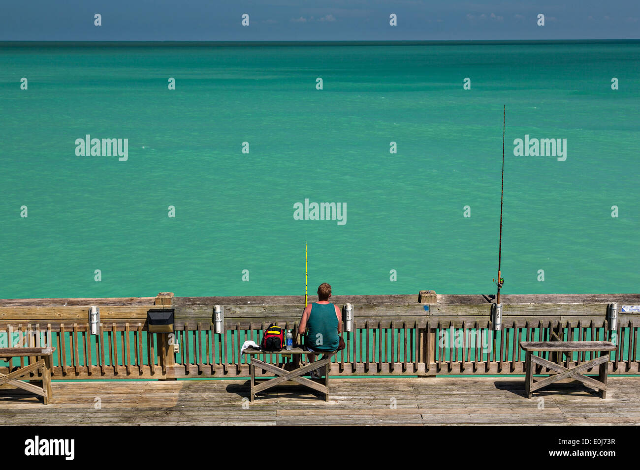 A fisherman waits for a catch on the pier at Folly Beach , SC Stock