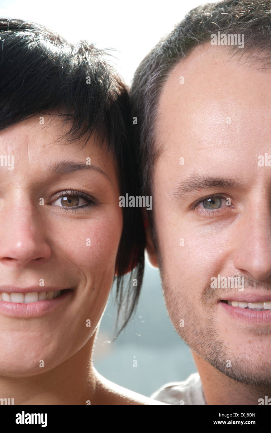 Young loving couple put their heads together and laugh - Stock Image