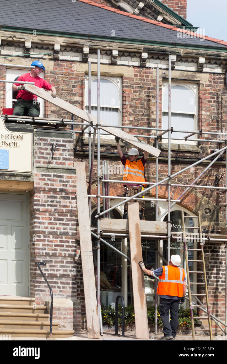 Three scaffolders building a scaffold passing planks to one another - Stock Image