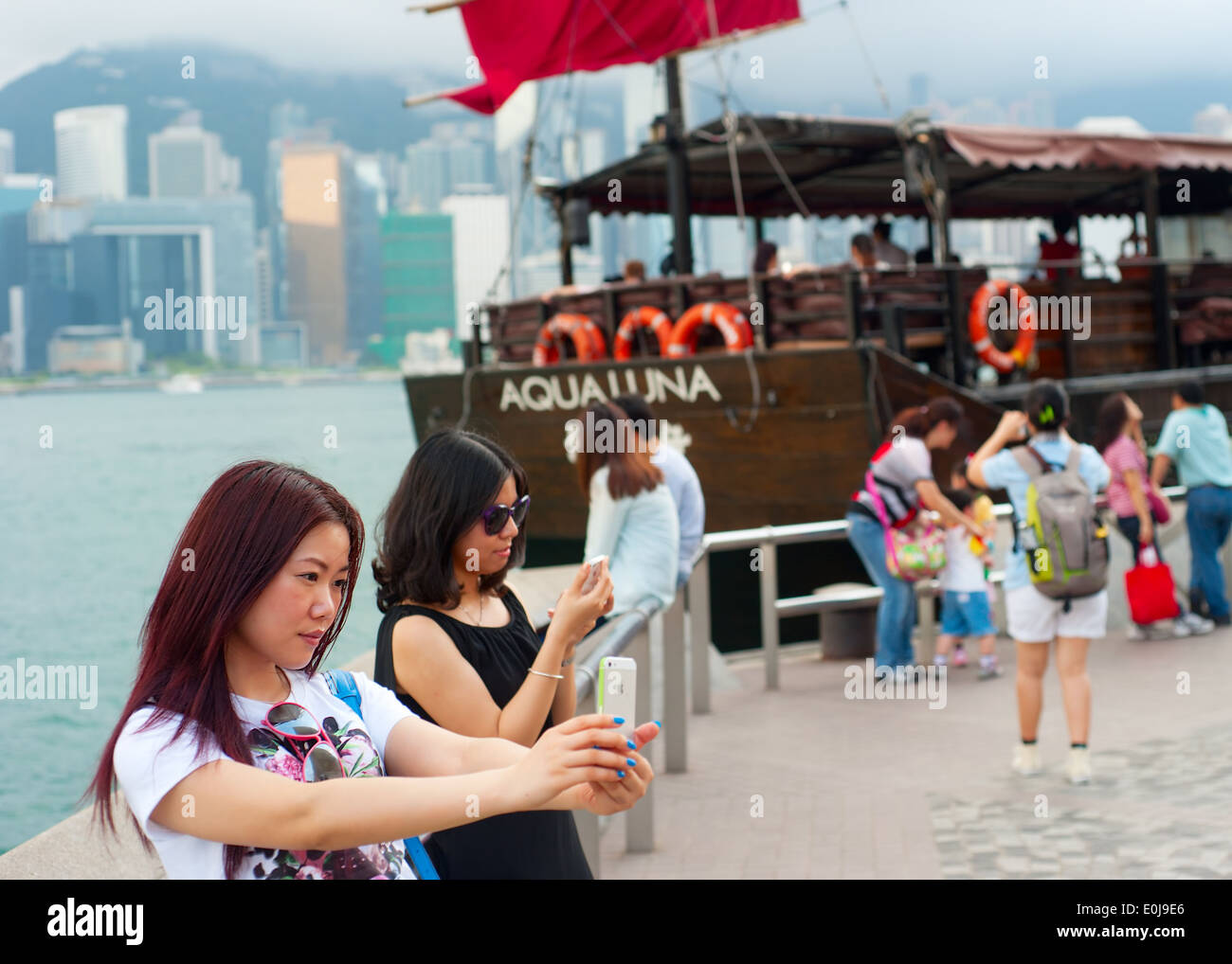 Pretty young female tourist makes selfie in Hong Kong. - Stock Image