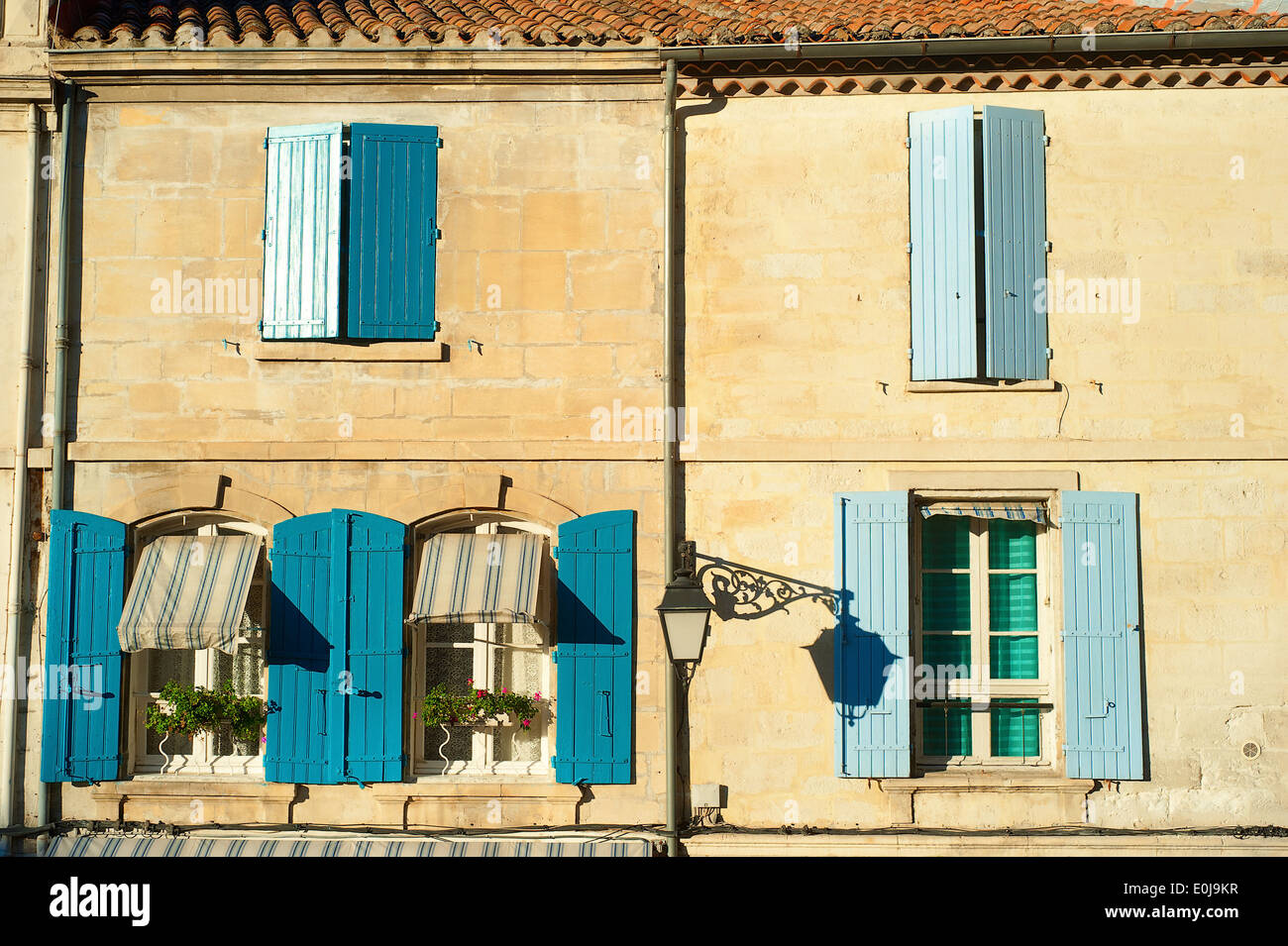 Typical building wall and windows at sunset in Arles, France - Stock Image
