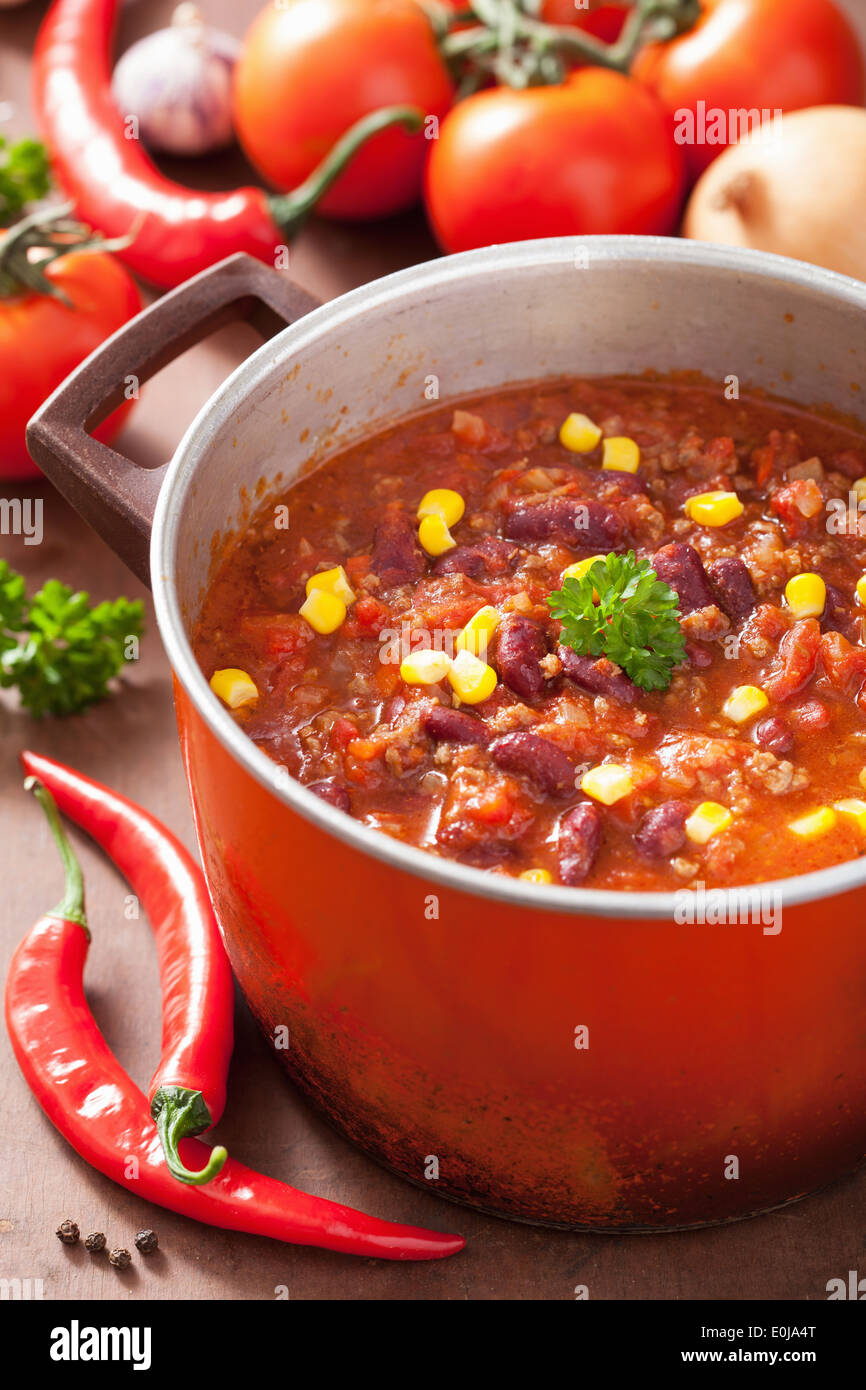 mexican chili con carne in red rustic pot with ingredients - Stock Image
