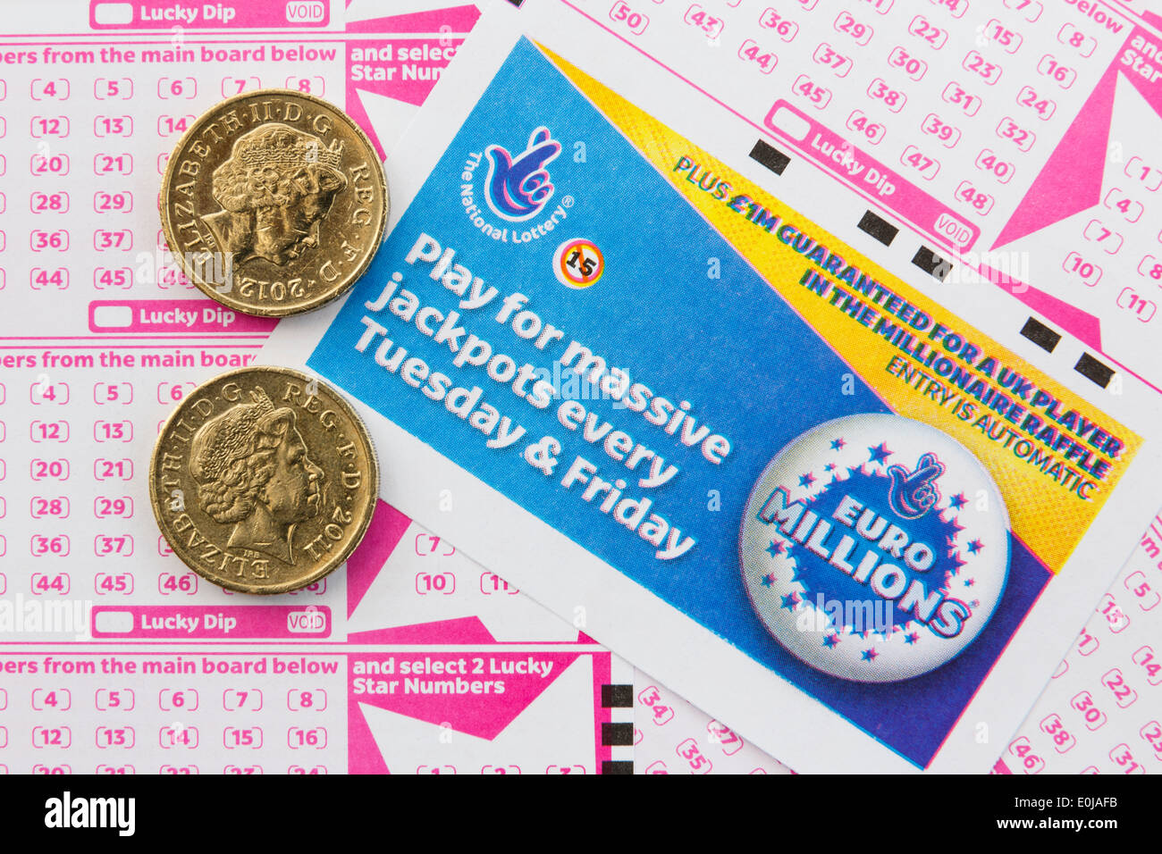 UK National Lottery Euro Millions payslips with number boards for selecting numbers and two £1 coins from above. England Britain - Stock Image
