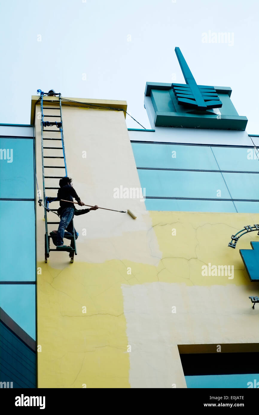 Local Painter Hanging Precariously From Ladder With No Safety Equipment As  He Paints The Side Of