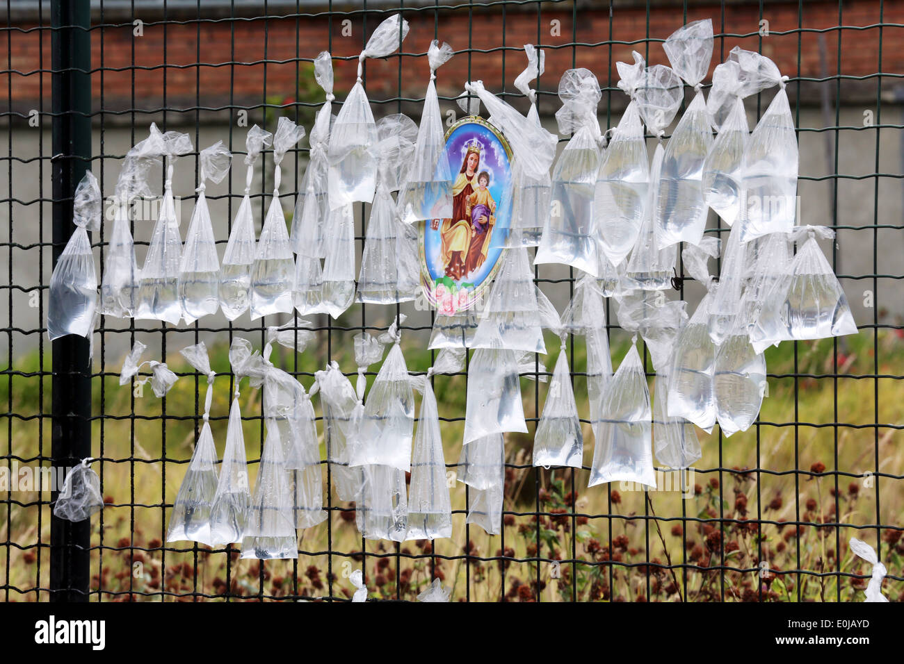 Tansparent plastic bags with water on a fence of the churchyard of nameless dead persons. Bogota, Colombia, South America - Stock Image
