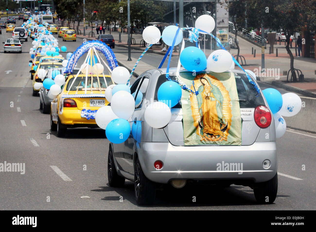 Parade of taxis decorated with balloons and statues of Mother Mary to honour the mother of Jesus Christ. Bogota, Colombia - Stock Image
