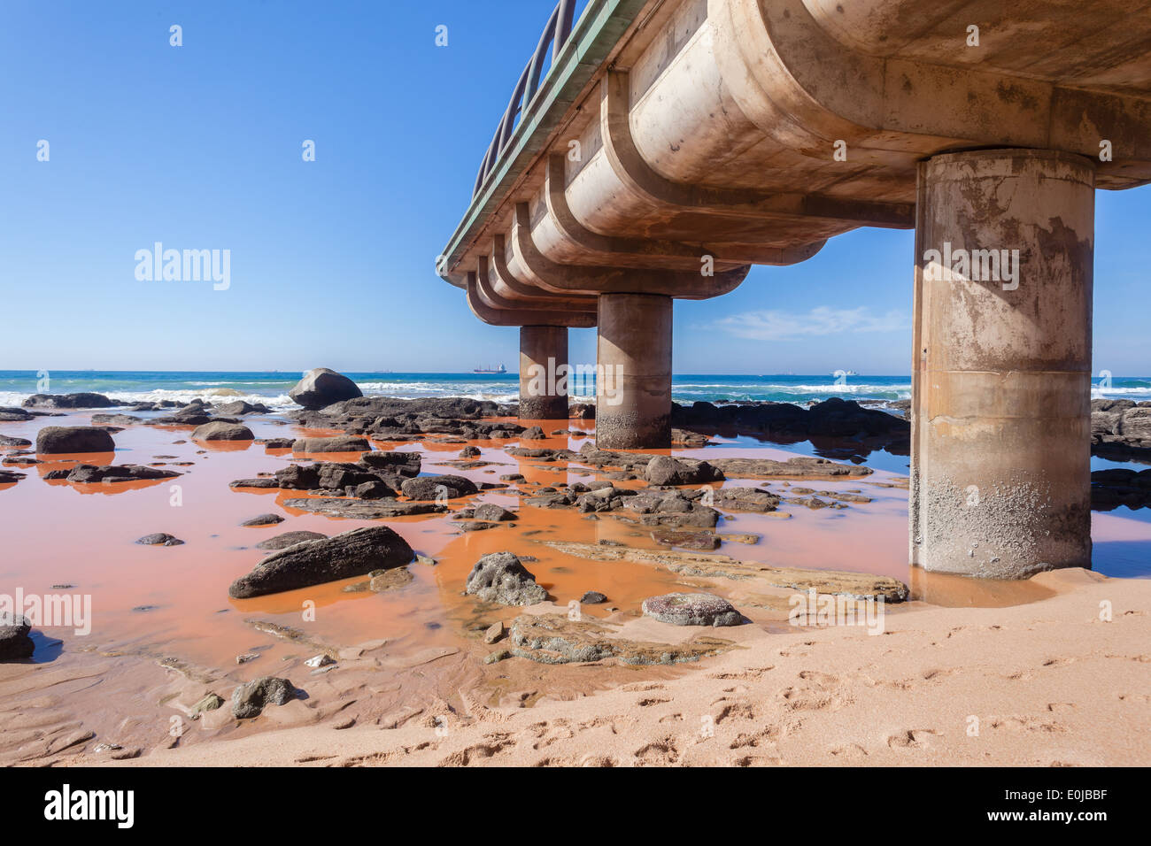 Pollution Industrial water liquid pours out into beach rocks and blue ocean sea waters coastline. - Stock Image