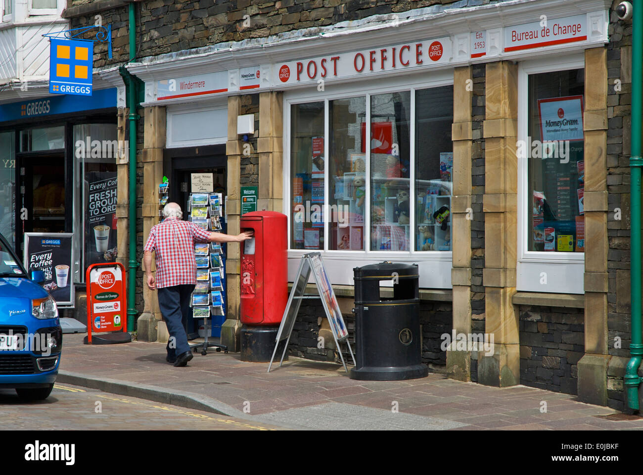 Man posting a letter in postbox outside post office, Cumbria, England UK - Stock Image