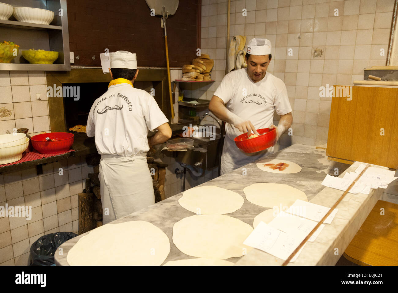 Cooks making pizza in the kitchen of Rome restaurant pizzeria making pizza pizzas cooks - Stock Image