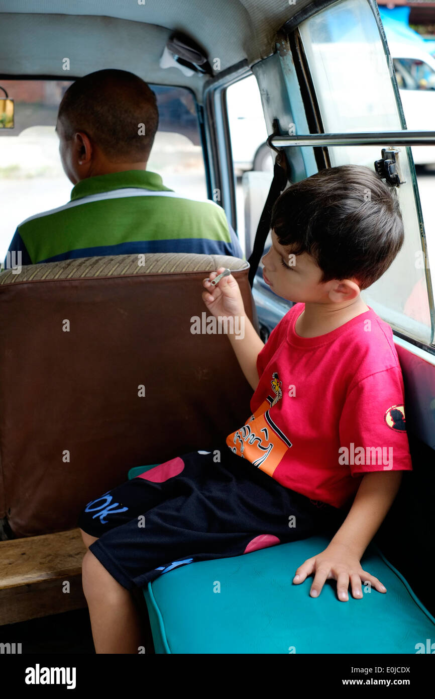 little boy amuses himself playing with a broken zipper he has found whilst a passenger in an angkot local transport - Stock Image