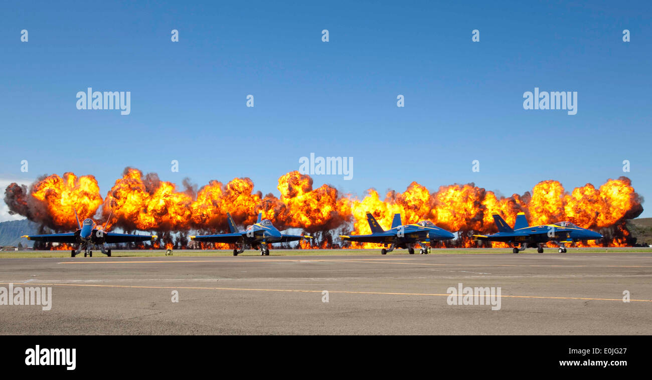 A fiery wall engulfs the clear Hawaiian sky behind the U.S. Navy's Flight Demonstration Squadron, the Blue Angels, during a M - Stock Image
