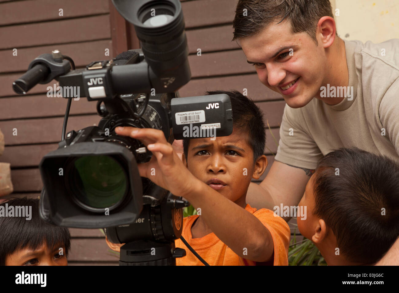U.S. Air Force Airman 1st Class, William Branch, Armed Forces Network - Okinawa, Japan, shows a local student how to record vid - Stock Image