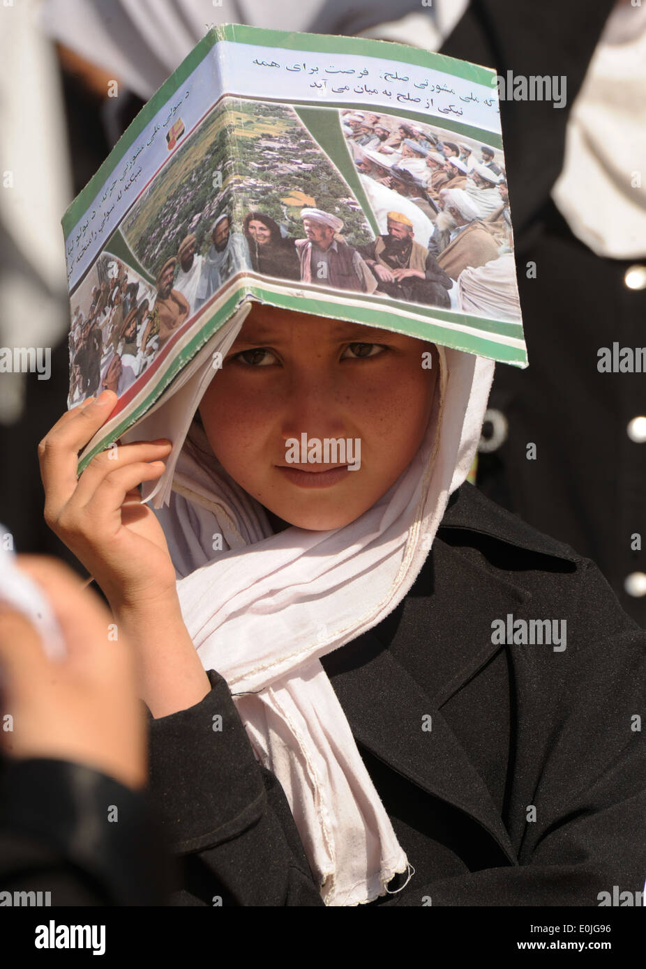 An Afghan girl uses a school book to shade her eyes from the sun as she waits for a ground breaking ceremony to begin at the Al - Stock Image