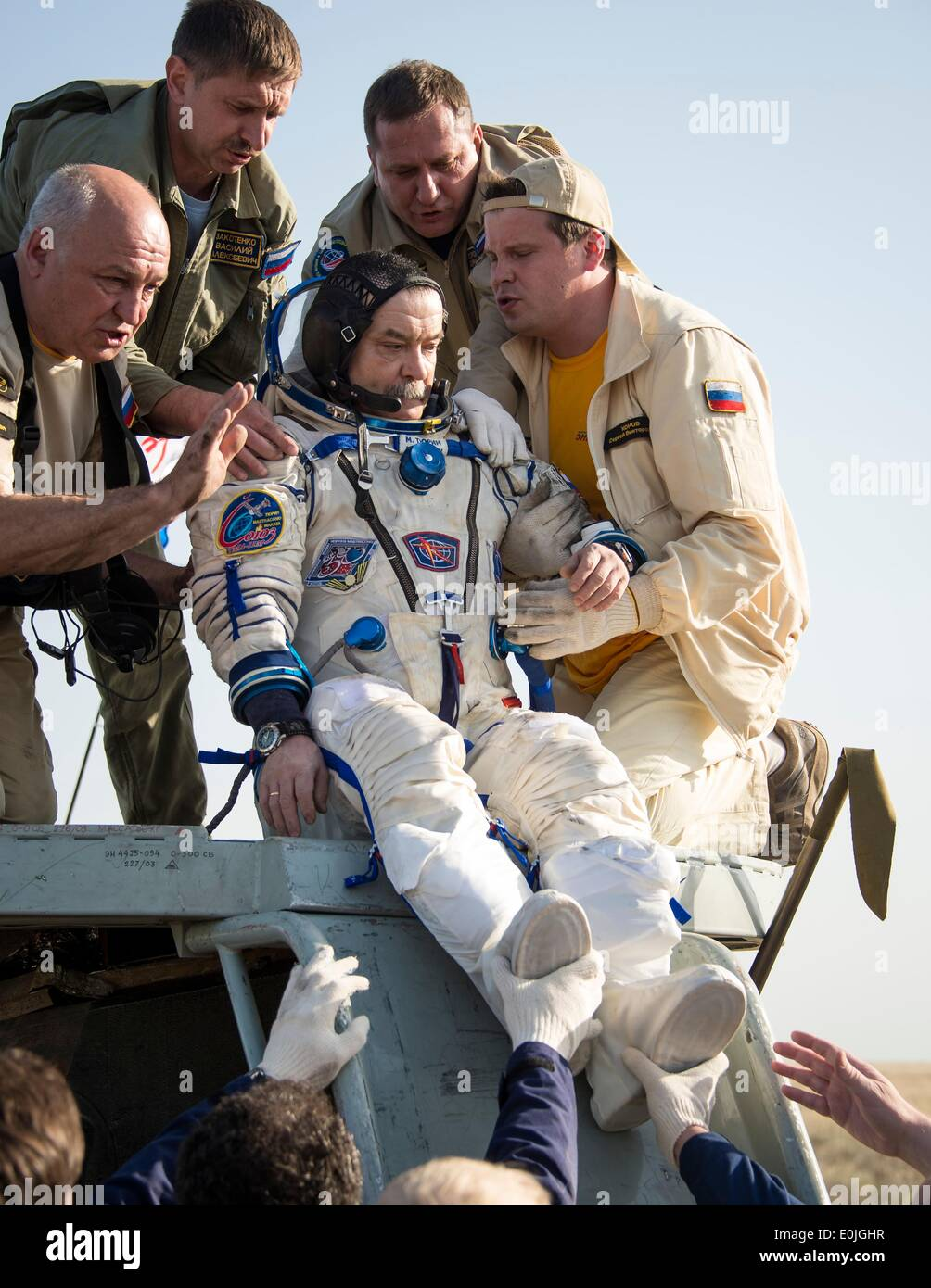 ISS Expedition 39 Soyuz Commander Mikhail Tyurin of Roscosmos is helped out of the capsule just minutes after landing with fellow expedition crew members in the Soyuz TMA-11M spacecraft May 14, 2014 near the town of Zhezkazgan, Kazakhstan. Wakata, Tyurin and Mastracchio returned to Earth after more than six months onboard the International Space Station where they served as members of the Expedition 38 and 39 crews. - Stock Image