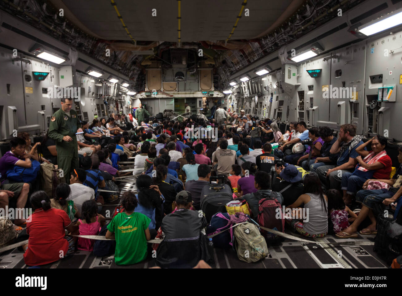 Displaced Filipino and other international personnel prepare for takeoff inside a C-17 Globemaster III with the 535th Air Lift - Stock Image