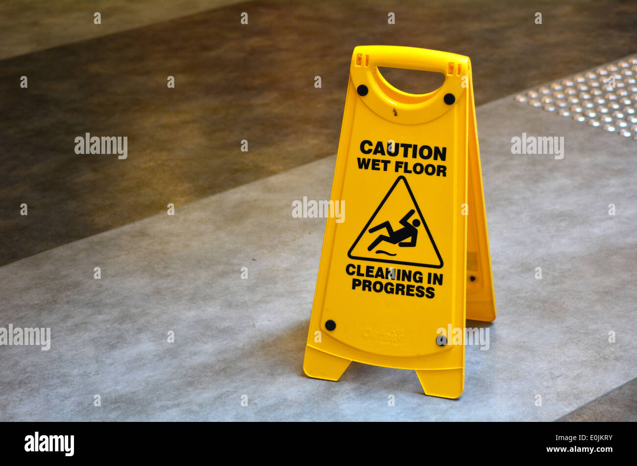 Slippery floor surface warning sign and symbol in building, hall, office, hotel , restaurant, restroom. Concept photo danger. - Stock Image