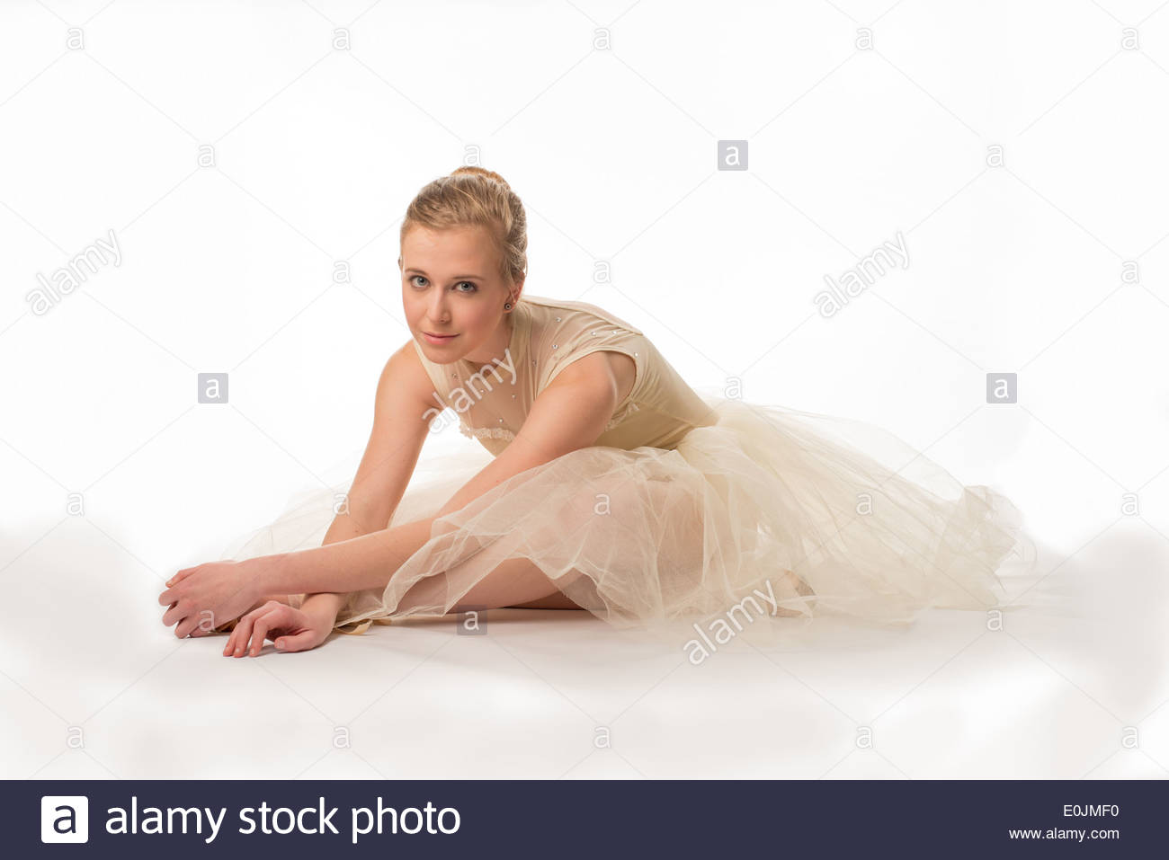 Teen girl in a white tutu on a white background sitting on the floor stretching. Stock Photo