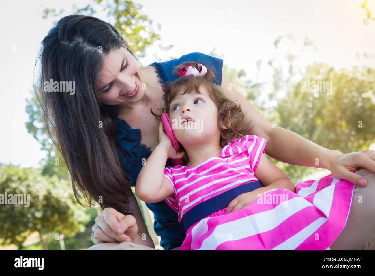 Mixed Race Mother and Cute Baby Daughter Playing with Cell Phone in Park. - Stock Image